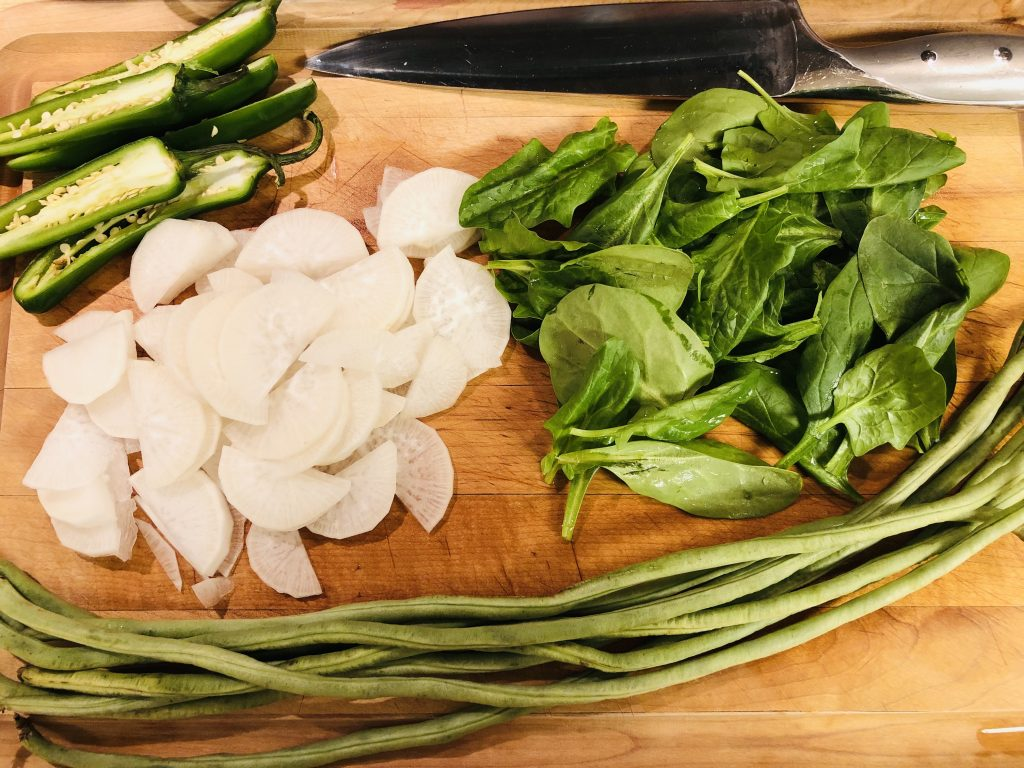 sitaw, spinach, daikon radish, serrano peppers sliced in half and a knife