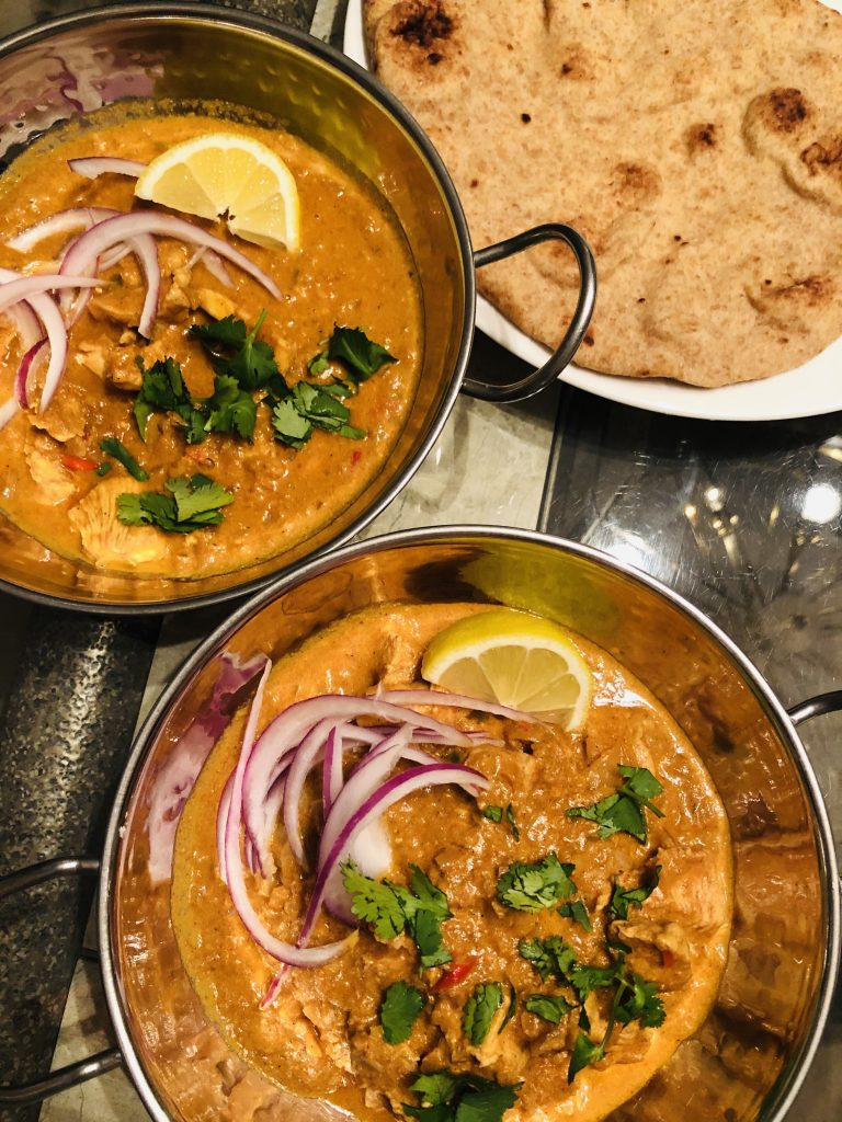 Indian Butter chicken in balti bowls with a naan bread on a white plate