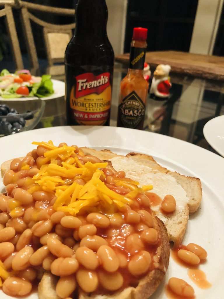 Beans on Toast with Worcestershire and Tabasco sauces and a salad in the background