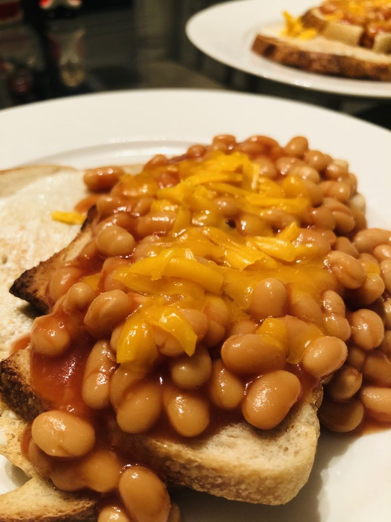 Cheddar cheese melting on beans on toast
