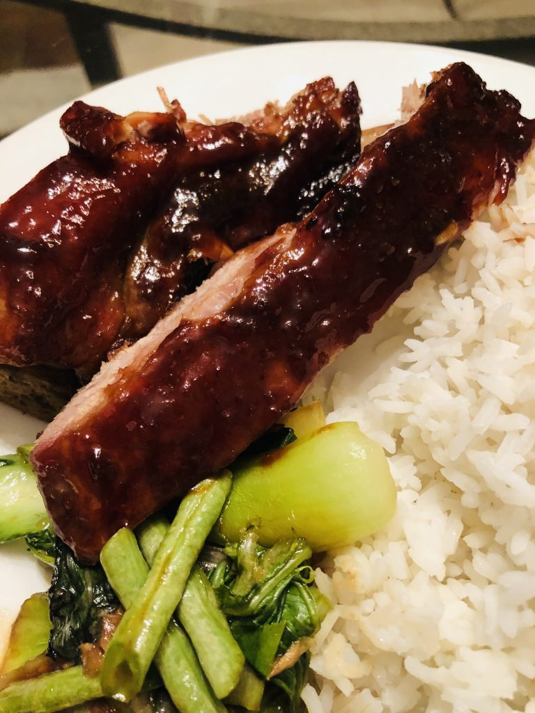 Chinese Barbecue Spareribs, rice and sauteed greens on a white plate