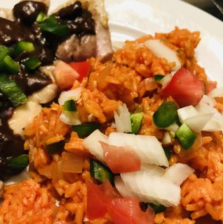 Mexican Rice served with chicken mole on a white plate garnished with onions, tomatoes, and jalapenos