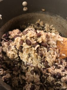 Cuban Black Beans and Rice in a saucepan with a wooden spoon with some of the beans and rice on it in the foreground
