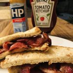 Bacon Sarnie on a white plate with HP Sauce and Heinz Tomato Ketchup in the background