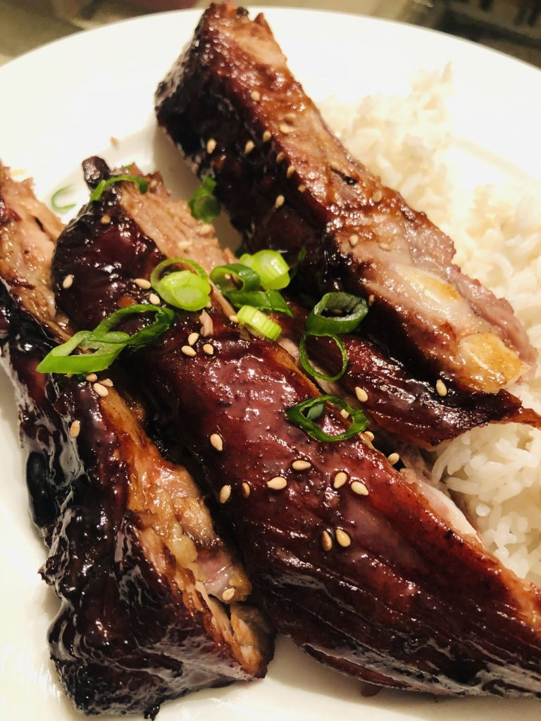 Chinese Barbecue Spareribs, rice and green onions on a white plate