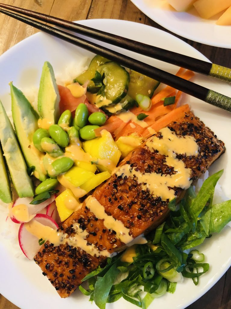 Salmon Rice Bowl with vegetables in a white bowl with chopsticks