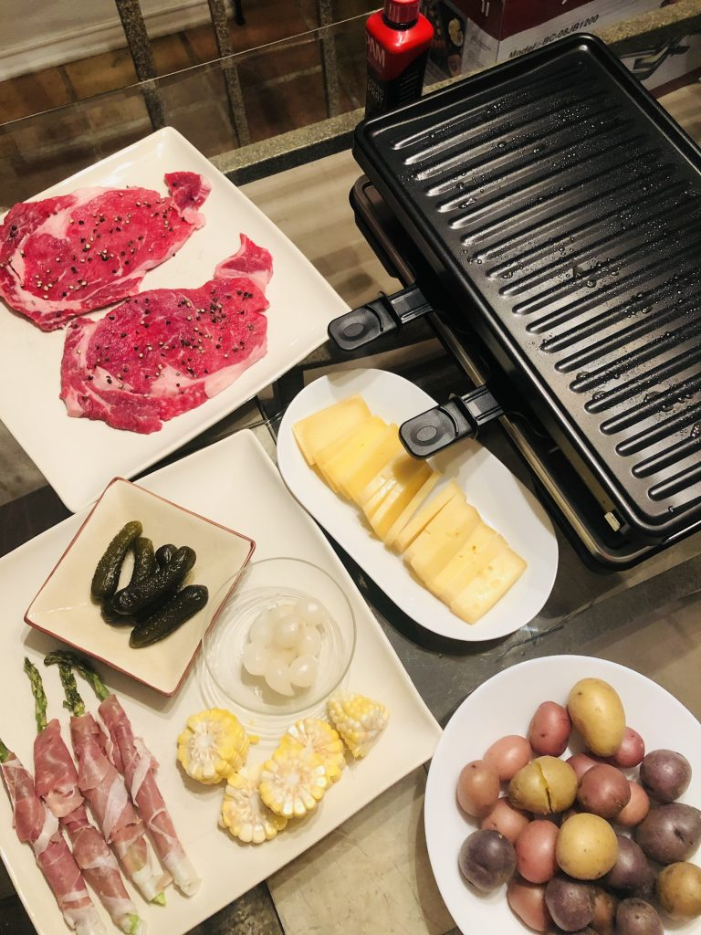 Raclette grill, steaks, prosciutto wrapped asparagus, raclette cheese, boiled new potatoes, gherkins, cocktail onions, sliced corn