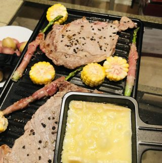 Raclette cheese, raclette grill with steaks, prosciutto wrapped asparagus, sliced corn, and boiled new potatoes