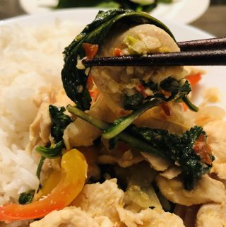 Chicken With Thai Basil served with rice and pair of chopsticks holding up the chicken