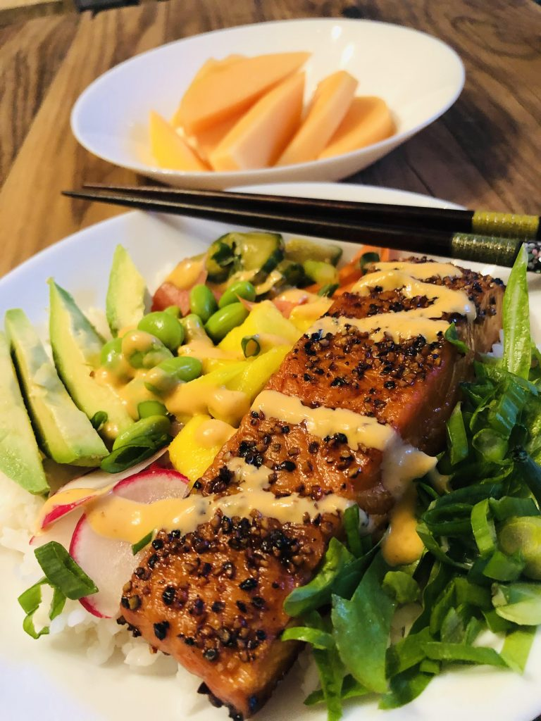 Salmon Rice Bowl with vegetables in a white bowl with chopsticks and cantaloupe in a white bowl