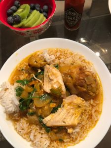 Belizean Stewed Chicken served with rice in a white bowl, with a jar of Tabasco and a bowl of kiwi slices and blueberries next to it