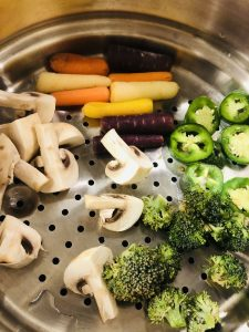 Baby carrots, cut up mushrooms, broccoli and jalapeños in a steamer