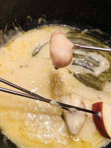 bits of apples and carrot on fondue forks in a cheese fondue pot