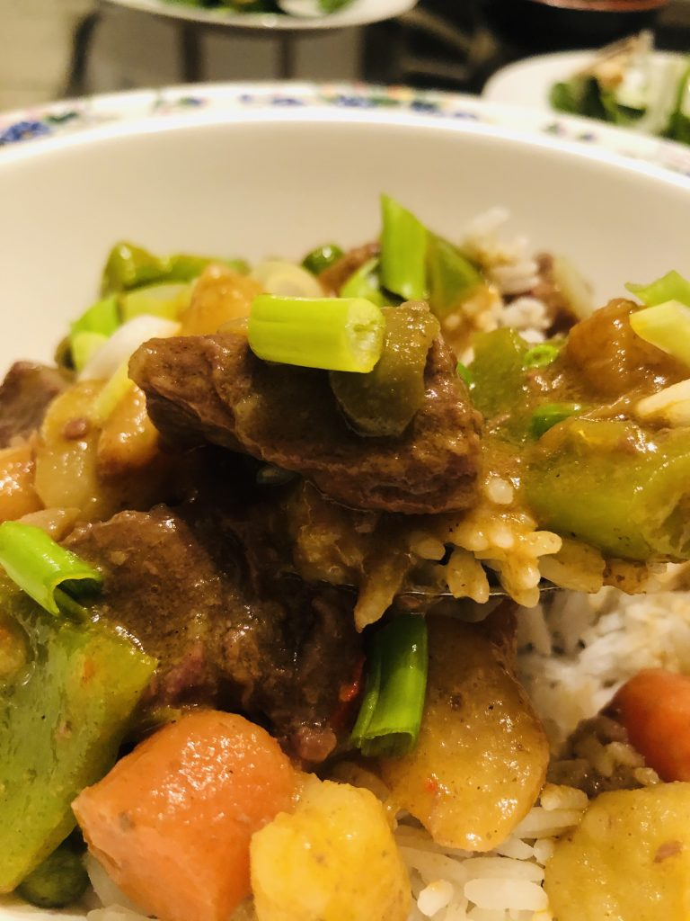 Beef caldereta served with rice in a bowl and garnished with sliced green onions