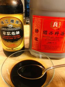 Dark Soy Sauce, Shaoxing Rice Wine and a glass bowl filled with a mixture of these 2 ingredients with a spoon