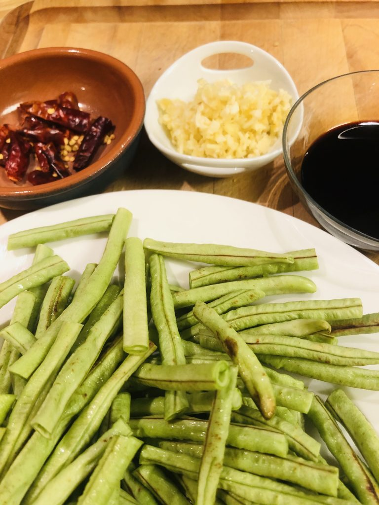 Chinese long beans cut into 3 inch pieces on a white plate, ground up Sichuan peppercorn in a small bowl, minced ginger and garlic in a small bowl, and a glass bowl with soy sauce and shaoxing rice wine