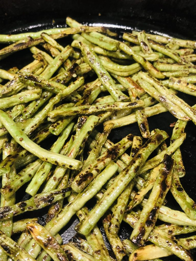 Chinese Long Beans cut into small pieces and cooked until charred in a cast iron pan