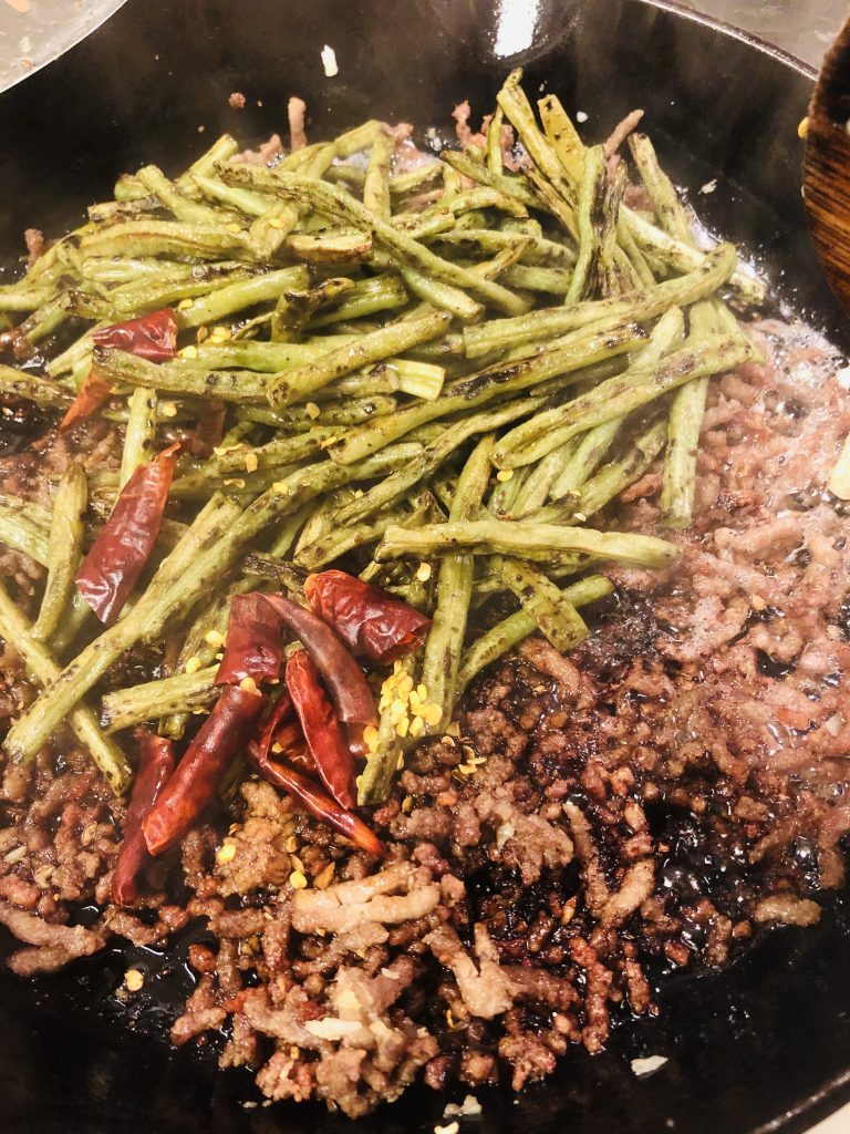 crispy ground pork, minced garlic and ginger, ground sichuan peppercorn, charred long beans, dried Asian Chilies and sauce in a cast iron skillet