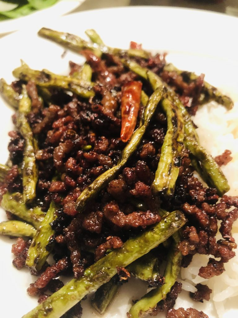 Chinese long beans with pork and dried Asian chilies on a white plate
