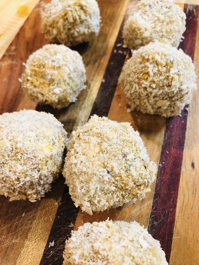Boudin Balls which have been breaded displayed on a wooden board