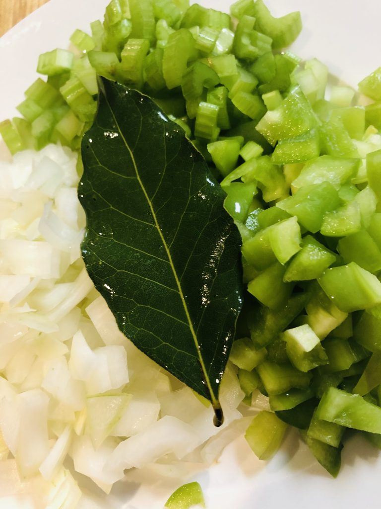 Diced onion, celery, and green bell pepper with a bay leaf on top