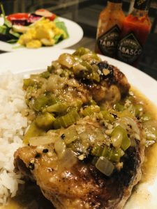 Cajun Smothered Chicken served with white rice on a plate with bottles of Tabasco in the background and a salad