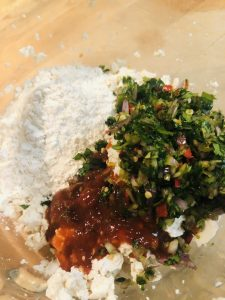 Minced herbs, shallot, and chilies, flour, sriracha sauce, and tofu in a mixing bowl