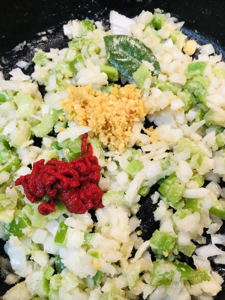 Diced green bell pepper, onion, and celery with bay leaf, minced garlic, and tomato paste
