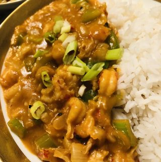 Crawfish Étouffée with white rice in a gold rimmed bowl