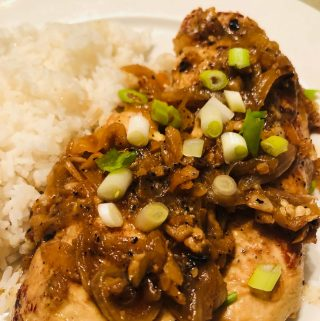 Chicken yassa with white rice and green onions on a white plate
