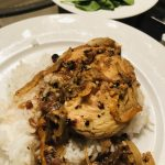 Chicken yassa and rice on a white plate