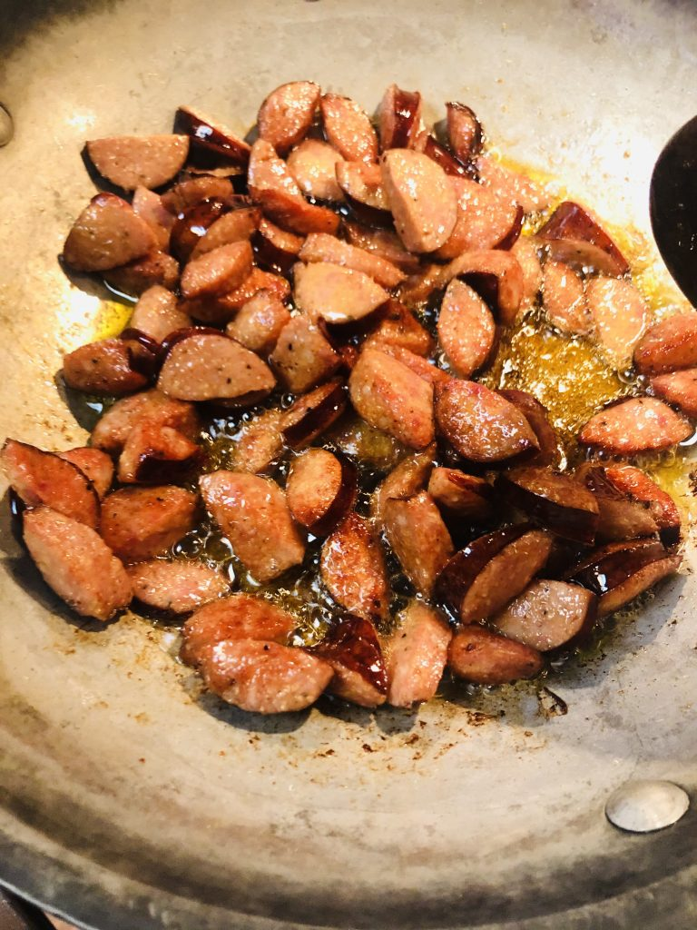 cut up pieces of andouille sausage being cooked in a skillet