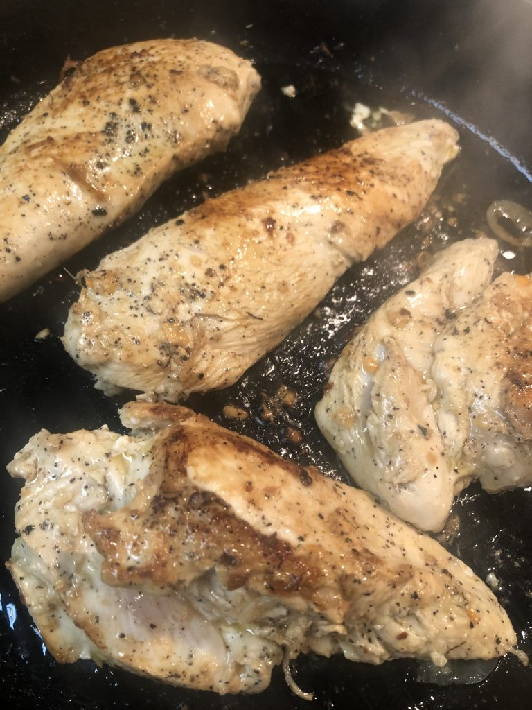 Browning chicken breasts in a cast iron skillet with olive oil