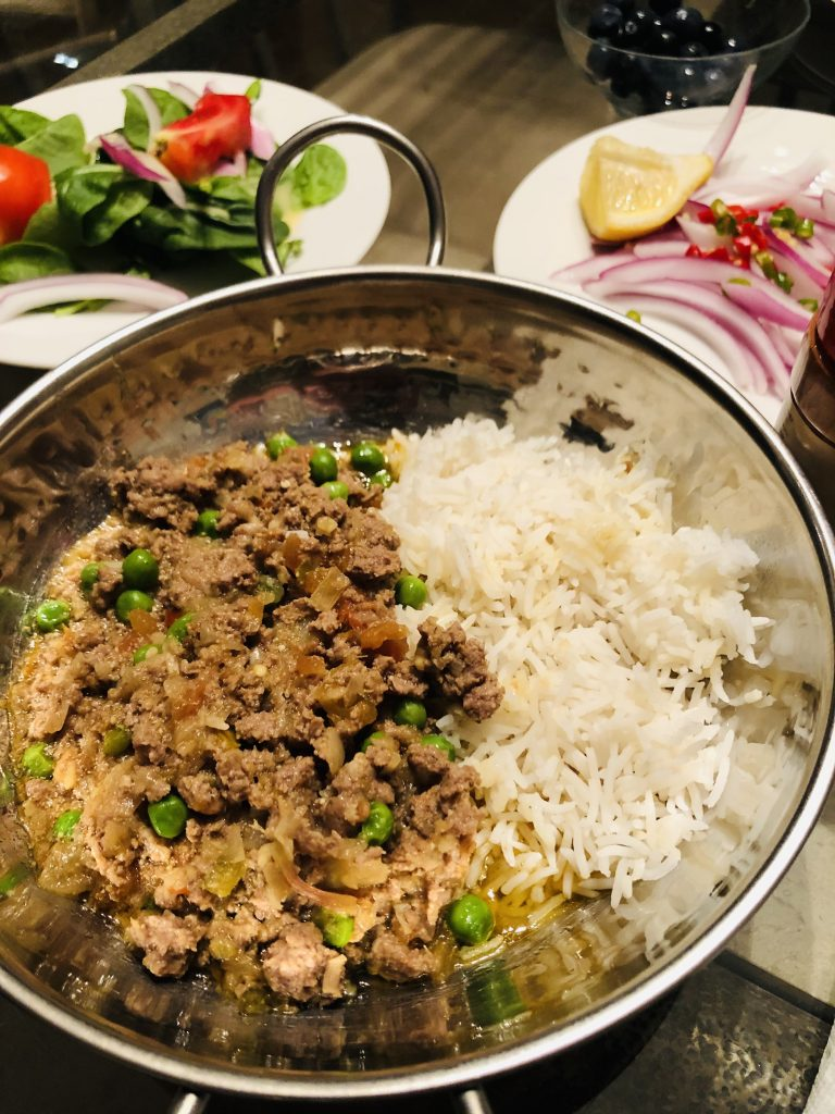 Keema do pyaza and white rice in a silver bowl, onion salad and spinach salad in the background on white plates
