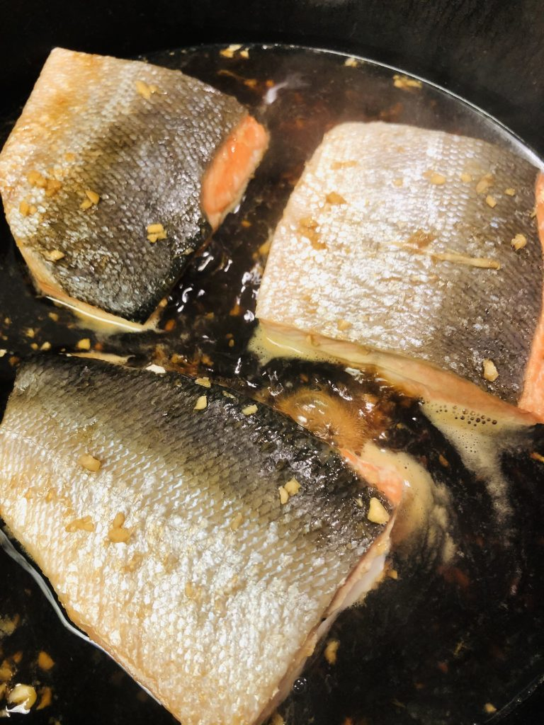 Pieces of salmon being poached in a cast iron pan
