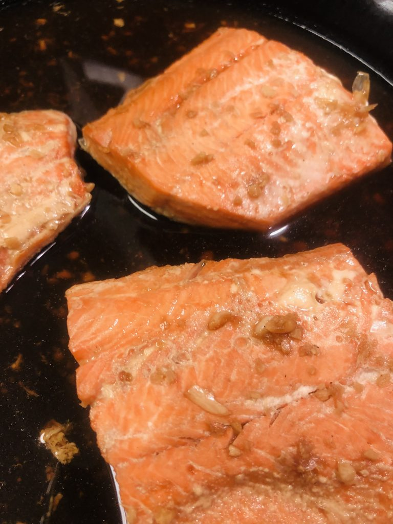 Salmon being poached in a cast iron pan