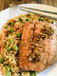 Asian Poached Salmon with fried rice in a white bowl and chopsticks on the side
