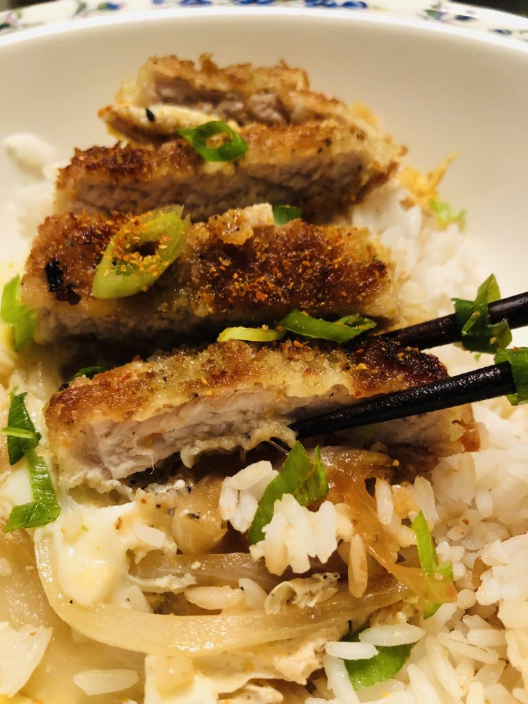 Japanese Pork Katsudon and Rice Bowl garnished with green onions and a piece of the pork cutlet held by chopsticks