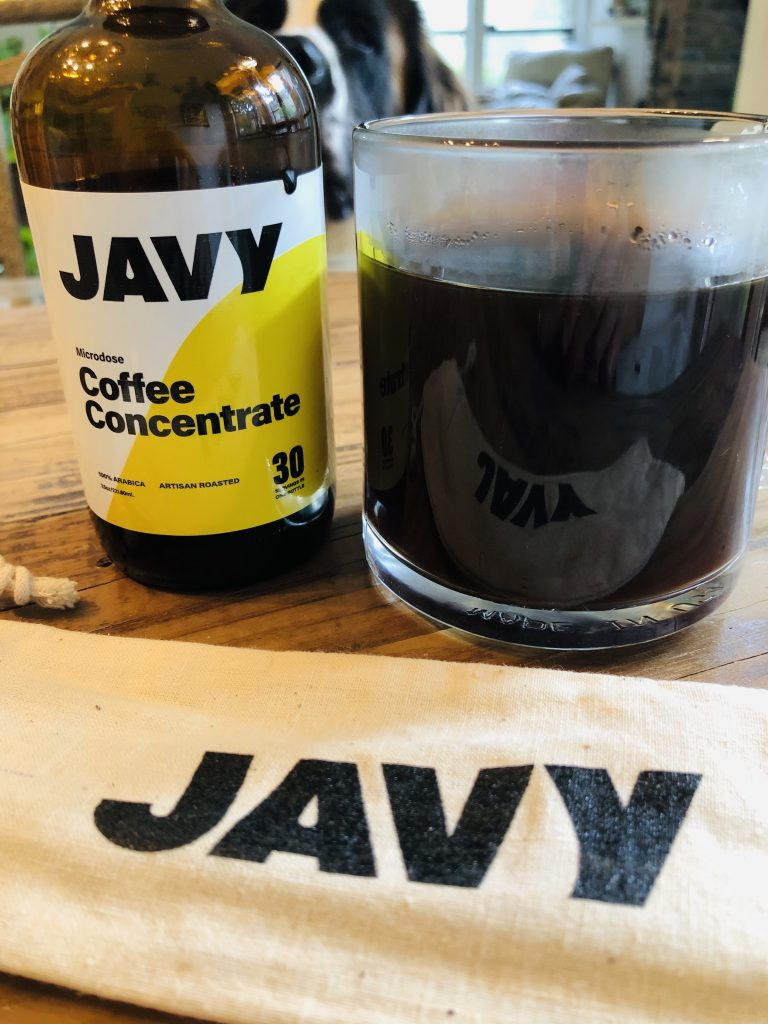 Javy coffee concentrate bottle alongside a glass filled with coffee and a cloth labeled with Jafy in front of these items