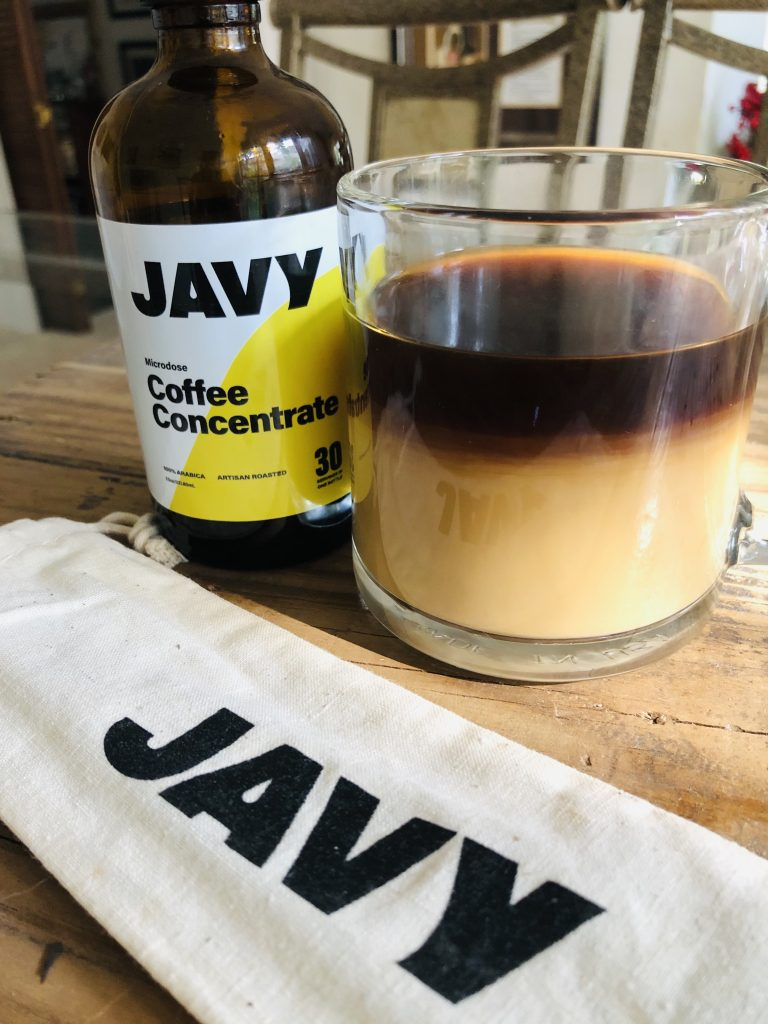 Javy coffee concentrate bottle alongside a glass filled with coffee and creamer and a cloth labeled with Jafy in front of these items