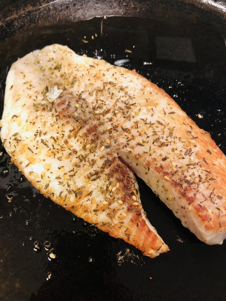 Browned and Cooked Tilapia With Za'atar in a cast iron pan