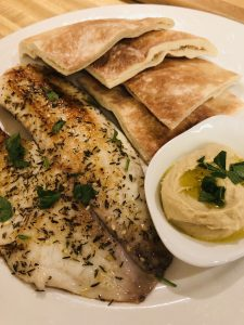 Tilapia With Za'atar garnished with parsley, pieces of pita bread, and hummus on a white plate
