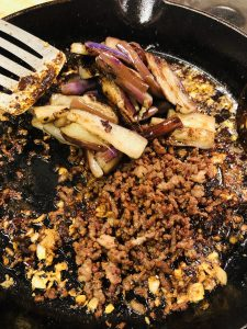 stir fried eggplant and crispy minced pork added to seasonings in a cast iron pan with spatula on the side