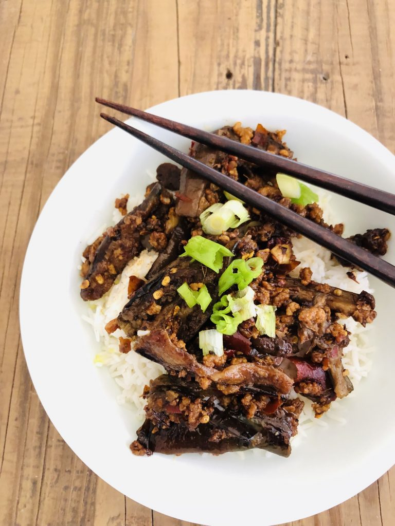 Sichuan eggplant with rice in a bowl and chopsticks on the side