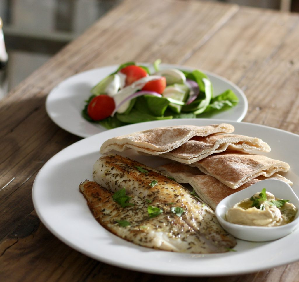 Tilapia With Za'atar garnished with parsley, pieces of pita bread, and hummus on a white plate with salad on a white plate behind the plate with the tilapia