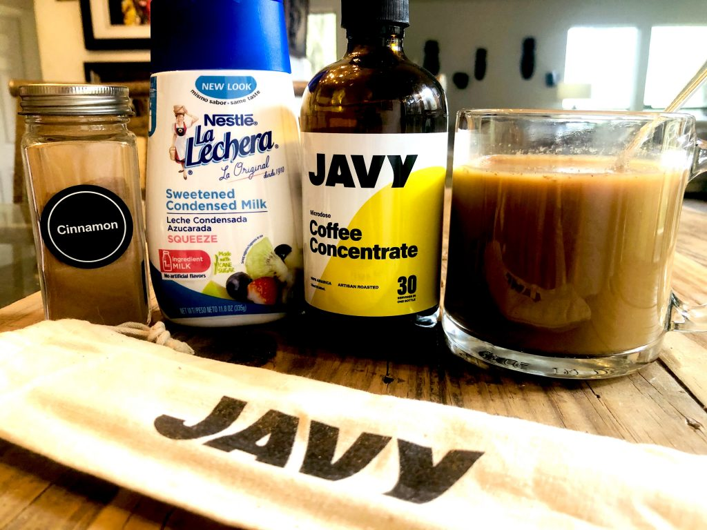 Javy coffee concentrate bottle alongside a glass filled with cold coffee, a glass bottle with cinnamon, a bottle of sweetened condensed milk, and a cloth labeled with Jafy in front of these items