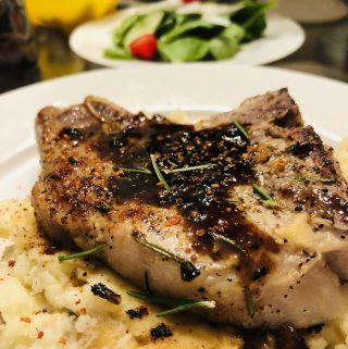 Pork chop with rosemary and caramelized sauce and mashed potatoes with a salad in the background