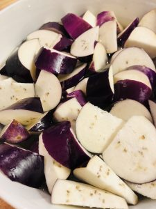 cut up pieces of Japanese eggplant in water in a white bowl