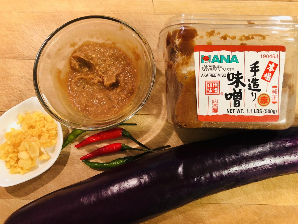 Japanese eggplant, Red miso paste in its package, thai chilies, minced garlic, and miso paste in a clear glass bowl