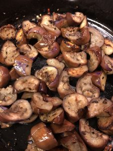 cut up pieces of Japanese eggplant being browned and cooked in a cast iron pan